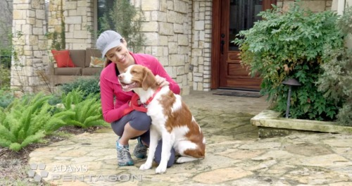 Woman and dog outside front door.