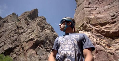 Climber standing in front of huge boulders.