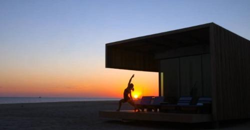 Women practicing yoga at dusk