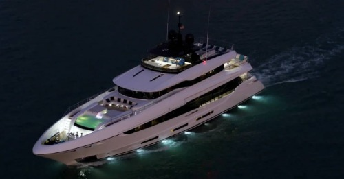 Yacht at sea with lights shining in water at nightfall.