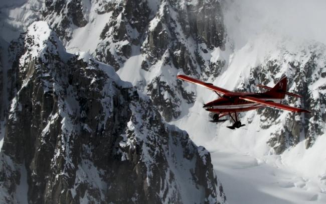 Bi-plane flying near mountains.