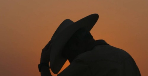Silhouette of man wearing a cowboy hat.